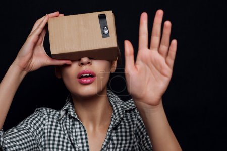 Color shot of a young woman looking through cardboard