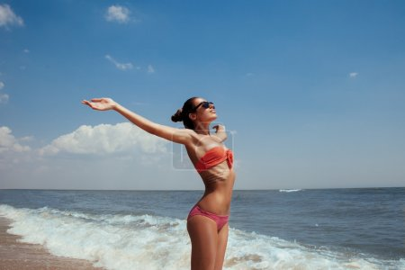 Beautiful young girl flying with seagulls on the sea