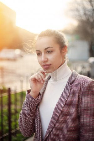 Photo for Young woman in jacket casual standing with city background at sunset.Sexy attractive woman with fashion styling.Image toned sunset - Royalty Free Image