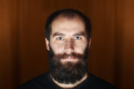 Portrait of tattooed bearded man wearing white blank t-shirt