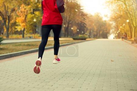 Fitness Girl running at sunset in city center