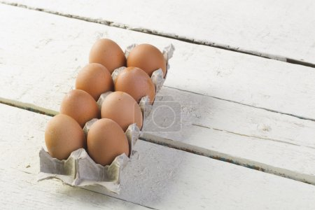 Eggs in a cardboard tray against white boards.