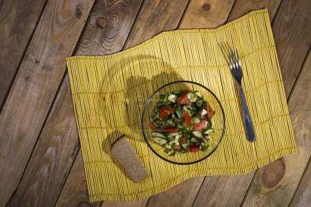 Salad and bread on a yellow bamboo mat on wooden background.