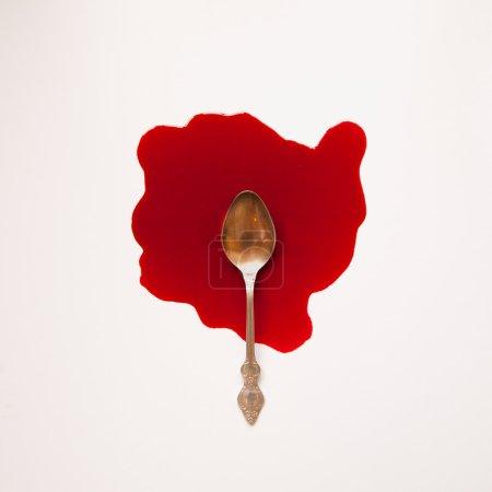 Foto de Cuchara en un charco de sangre sobre un fondo blanco - Imagen libre de derechos