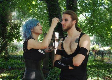 Halloween woman doing makeup to a man...