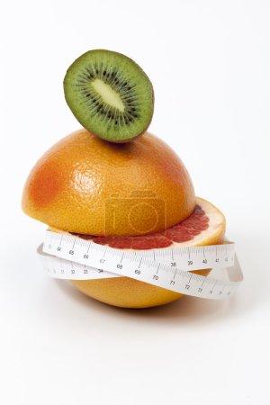 Half sliced red grapefruit and kiwi and tape measure around