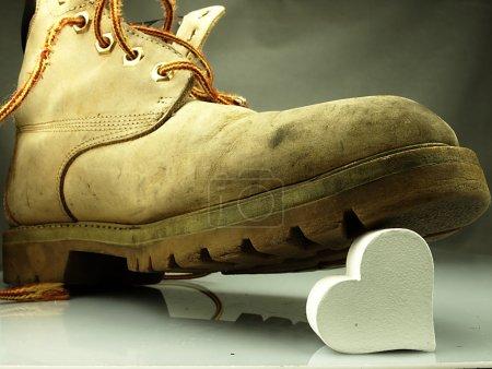 Photo pour Bottes militaires anciennes, très lourdes piétinant un cœur blanc délicat . - image libre de droit
