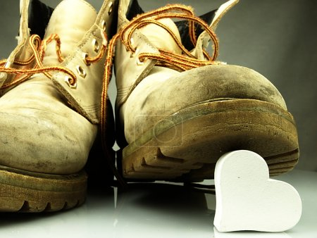 Photo pour Bottes militaires anciennes, très lourdes, piétinant un cœur blanc délicat . - image libre de droit