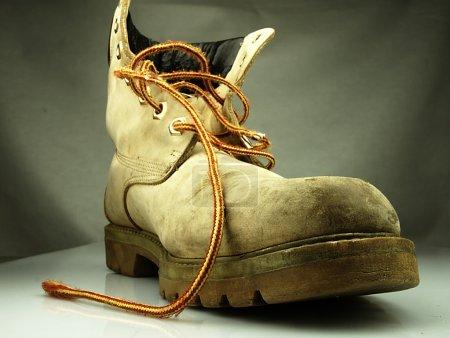 Photo pour La vieille chaussure lourde et sale. Seule et sans l'autre chaussure . - image libre de droit