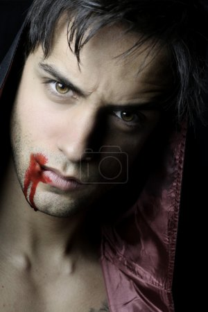 Portrait of a beautiful vampire with blood flowing...