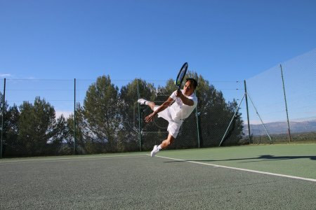 Tennis player dives to catch a ball