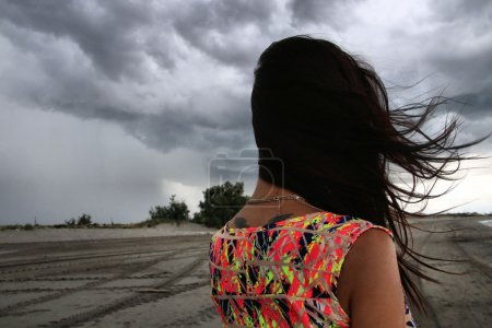 Photo for Young woman looking at a storm on the beach - Royalty Free Image