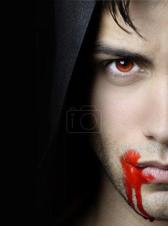 Portrait of an handsome vampire over a black backg...
