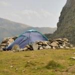 Alpine tent and windbreak from rocks in Carpathian...