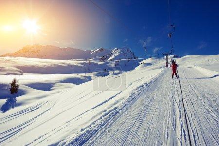 Person on ski lift in mountains