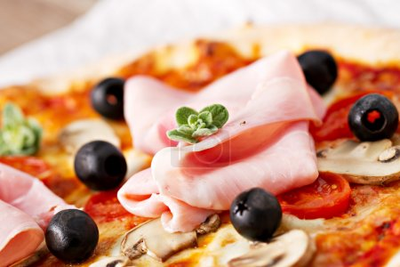 Pizza with olives, ham and mushrooms
