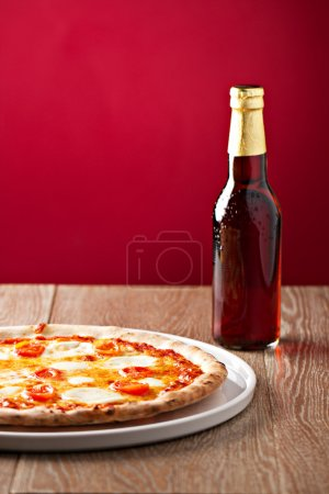 Pizza margherita and bottle of beer