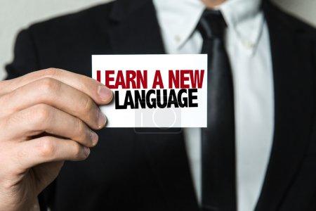 Foto de Empresario sosteniendo la tarjeta con el texto: aprender un nuevo idioma - Imagen libre de derechos