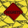 Regrets written on multiple road sign...
