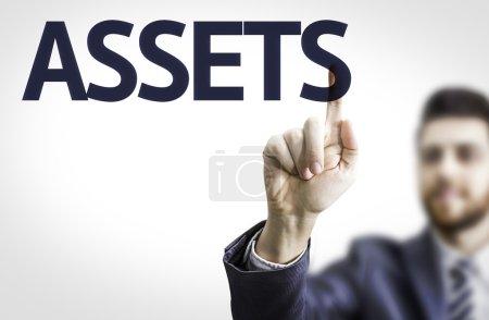 Photo pour Homme d'affaires pointant vers un tableau transparent avec le texte : Actifs - image libre de droit