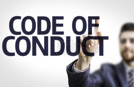 Photo pour Homme d'affaires pointant vers un tableau transparent avec le texte : Code de conduite - image libre de droit
