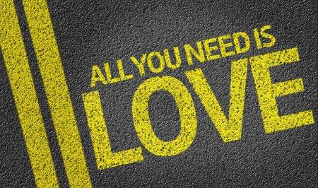 Photo pour Tout ce dont vous avez besoin est amour écrit sur le fond de la route - image libre de droit