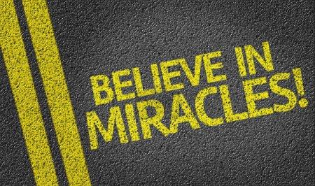 Photo pour Croyez aux miracles ! écrit sur le fond de la route - image libre de droit