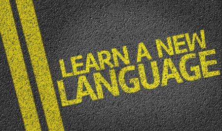 Foto de Aprender un nuevo idioma escrito en el fondo del camino - Imagen libre de derechos