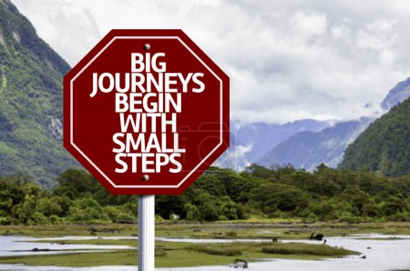 Photo pour Big Journeys Begin With Small Steps written on red road sign with landscape background - image libre de droit