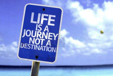 Photo pour La vie est un voyage pas un panneau de destination avec une plage sur fond - image libre de droit
