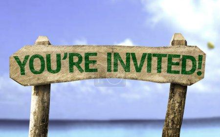 Photo pour Vous êtes invités ! panneau en bois avec une plage sur le fond - image libre de droit