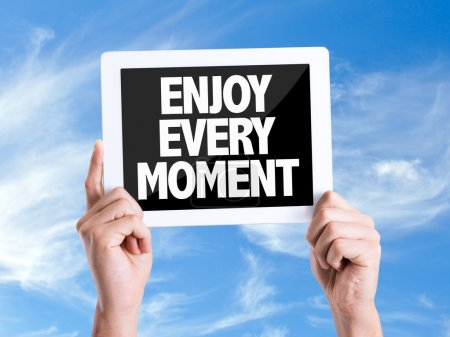 Photo pour Tablette pc avec texte Profitez de chaque instant avec fond de ciel - image libre de droit