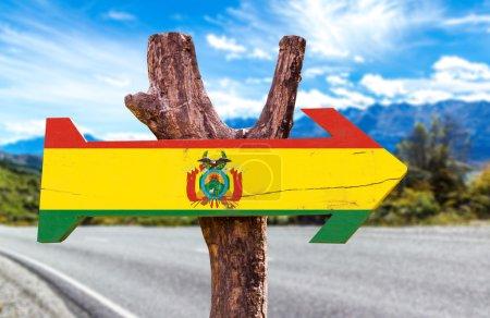 Photo pour Bolivie Drapeau panneau en bois avec fond de route - image libre de droit