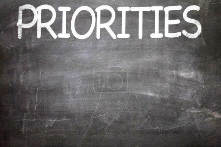 Priorities white letters written on a chalkboard...