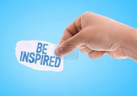 Photo pour Pièce de papier avec les mots Be Inspired avec fond bleu - image libre de droit