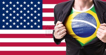 Photo pour Homme d'affaires qui s'étend de costume avec drapeau brésilien sur fond de drapeau américain - image libre de droit