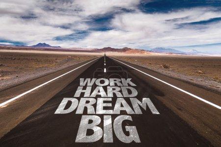 Photo pour Travailler dur Dream Big écrit sur la route du désert - image libre de droit