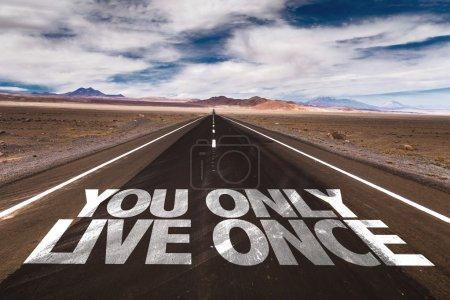 Photo pour Vous Only Live Once écrit sur la route du désert - image libre de droit