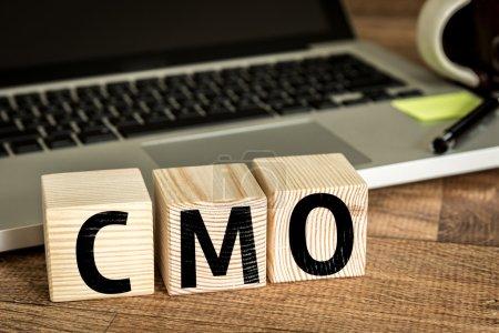 CMO written on a wooden cubes