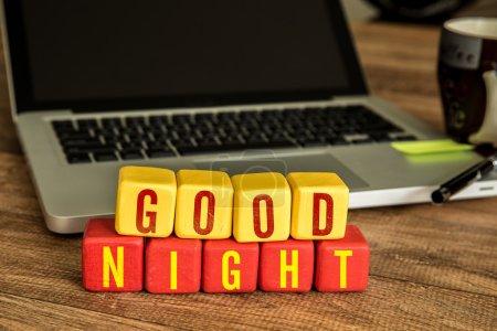 Photo pour Bonne nuit écrite sur un cube en bois dans un bureau - image libre de droit