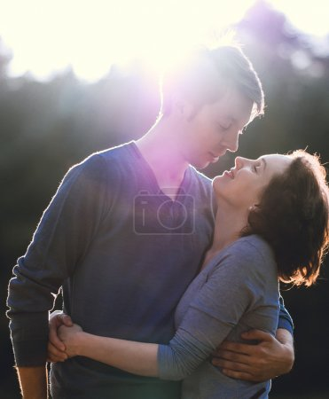 Nice beautiful romantic couple kissing in sunset light