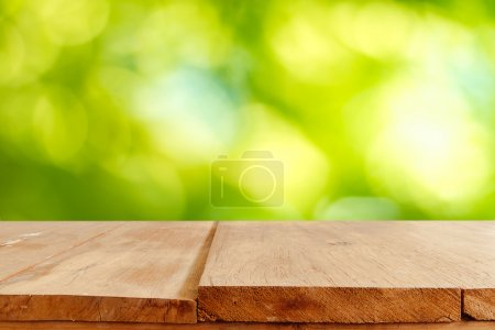 Empty wooden table and green natural spring blur bokeh backgroun