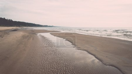 Shoreline of Baltic sea beach with rocks and sand dunes. Vintage