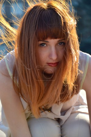 Portrait of red-haired girl, strands in the wind