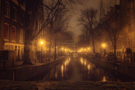 Photo pour Un pont canal à Amsterdam la nuit, avec reflets & silhouette - image libre de droit