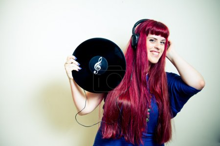 Young pretty woman dancing with headphones and vinyl record