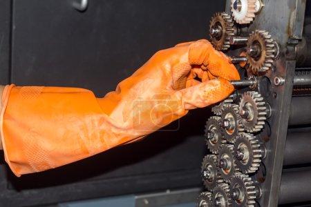 Gloved hands repairing gears of photo printer