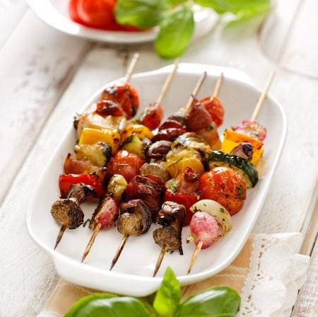 Grilled skewers of vegetables and meat in a herb marinade on white plate