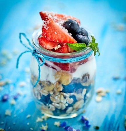Strawberry blueberry yogurt parfait with addition of muesli, coconut flakes and fresh mint