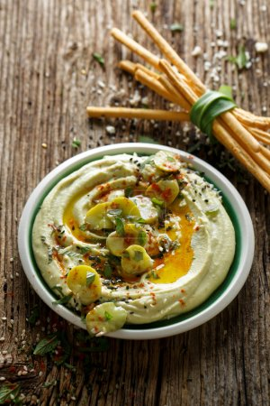 Broad bean hummus, with addition of olive oil, paprika powder, fresh mint and sesame seeds,  delicious and healthy vegan dip or spread